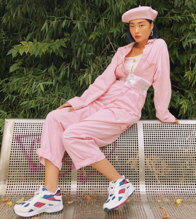 short hair girl wearing a white top, pastel pink denim jacket, baggy pastel pink pants, white sneakers with pink and blue, pastel pink beret