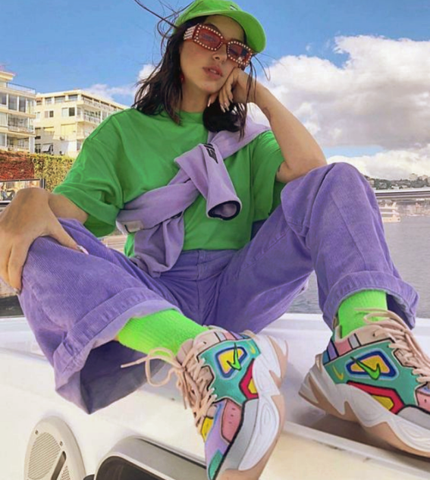 girl with long brown hair wearing a neon green baseball cap, neon oversized shirt, purple corduroy pants, neon socks, lilac fanny pack, white sneakers with blue, pink, red and yellow