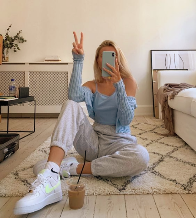 blonde girl with light blue top with dropped sleeves, white pants, white tennis shoes