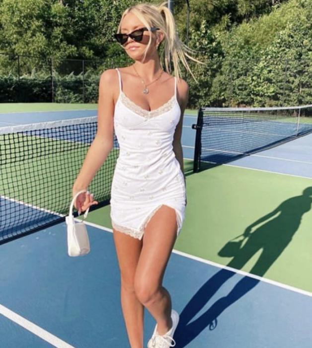 chica rubia con lentes de sol, vestido blanco de satén tipo camisón con encaje, tenis blancos y bolso pequeño blanco