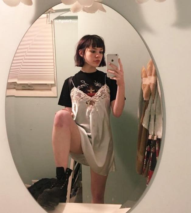 chica de cabello corto oscuro usando una camiseta negra, vestido blanco de satén con encaje tipo camisón, botines negros de cuero