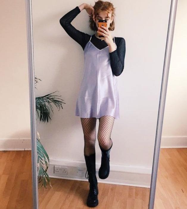 chica pelirroja con vestido de satén lila de tirantes tipo camisón, top negro de manga larga, medias negras semitransparentes, botines negros de cuero