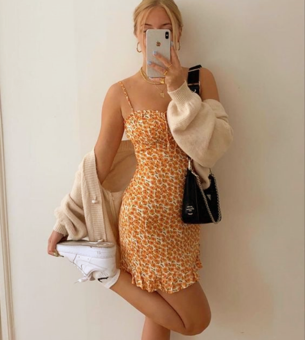 blonde girl in orange sundress with yellow tight with white tennis shoes, beige cardigan and black handbag