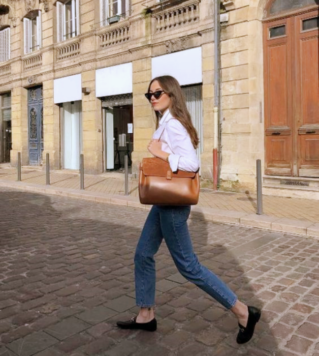 light-haired girl with sunglasses, white dress shirt, skinny jeans, black flats and brown leather bag