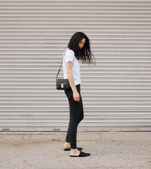 girl with dark hair, white shirt, tight black jeans, black flats and black leather bag