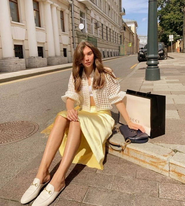 light haired girl wearing white puff sleeve blouse, yellow satin skirt, white leather flats loafers