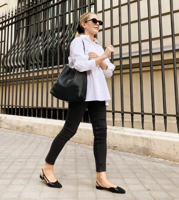 blonde girl with sunglasses, oversized white shirt, tight black jeans, black flats and black leather handbag