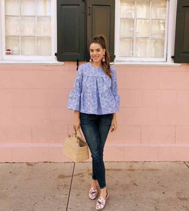 brown haired girl wearing baggy light blue blouse, skinny jeans, pink flats with coffee