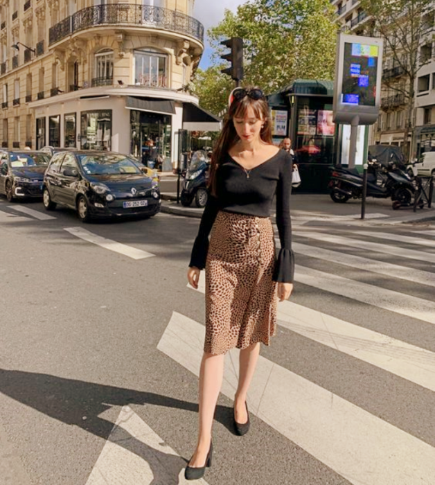 brown haired girl wearing long sleeve black blouse, brown midi skirt, black flats
