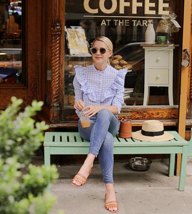 chica de cabello rubio con lentes de sol, blusa azul celeste de cuadros blancos, jeans ajustados y flats beige claro