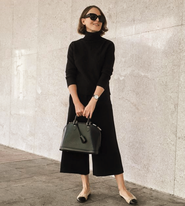 short brown hair girl wearing sunglasses, long sleeve black blouse, black culottes, beige flats with black tip