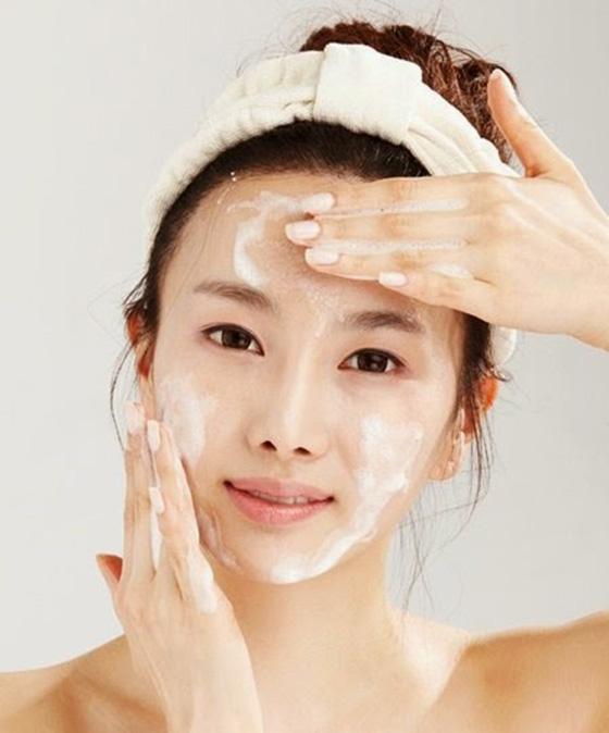 Chica limpiando su rostro frente al espejo; 'Saho', el ritual para cuidar de tu piel con un toque japonés