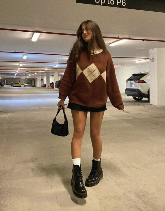 chica llevando outfit estilo colegial con sueter amplio y botas militar;13 Outfits colegiales por sí extrañas tus días de escuela