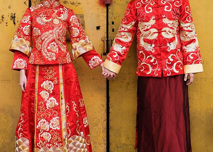 pareja de novios chinos agarrados de la mano con vestimenta típica de la cultura china