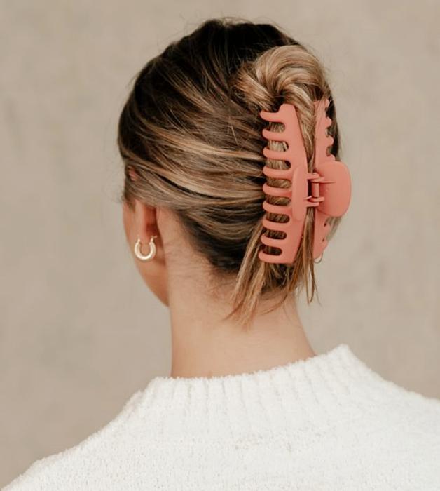 chica rubia con top blanco, pinza para el cabello rosa larga