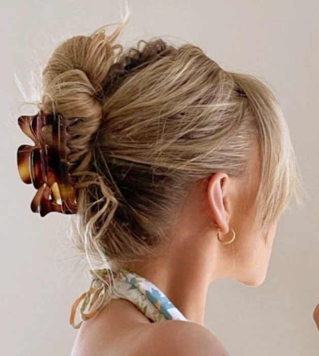 blonde girl with brown, beige, yellow hair clip, with blue halter top with white