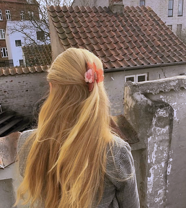 blonde girl with coral pink hair clip, gray knitted sweater