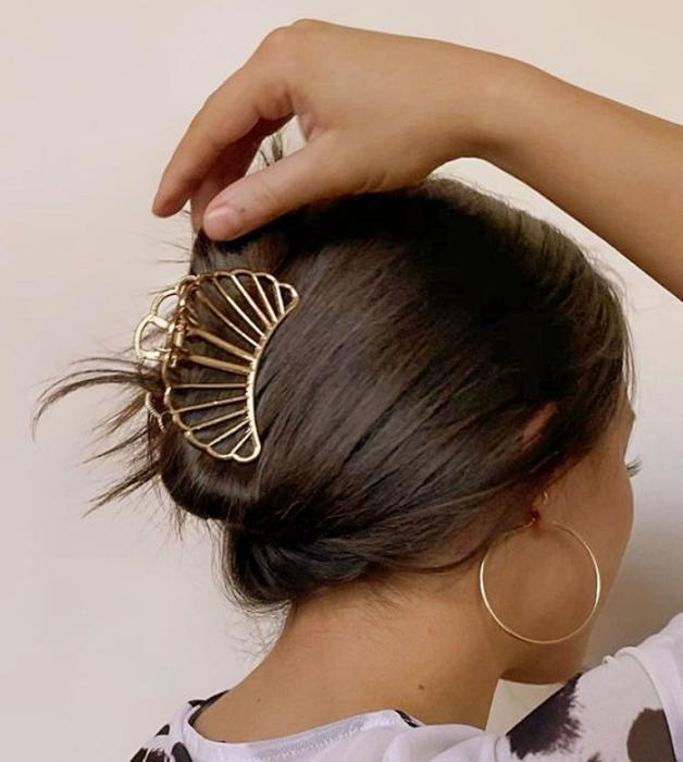 chica de cabello castaño usando una pinza para el cabello de metal en forma de coral, blusa blanca con negro