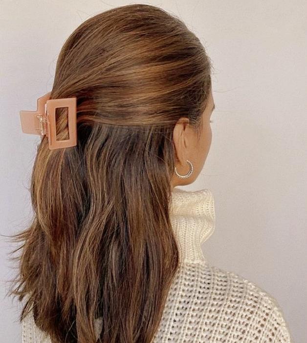 chica de cabello castaño largo usando una pinza para el cabello color rosa coral cuadrada, suéter beige tejido de cuello