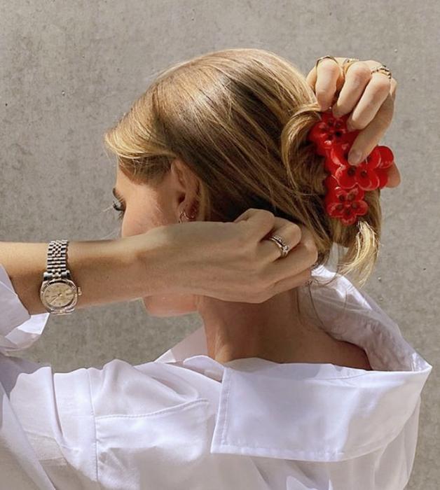 chica rubia usando una pinza para el cabello roja con camisa blanca de vestir y reloj plateado