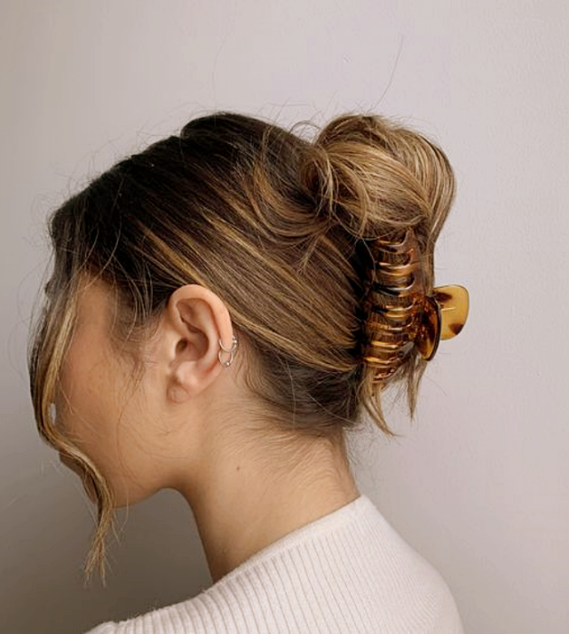 light haired girl wearing brown tortoise clip with beige and amber, white top