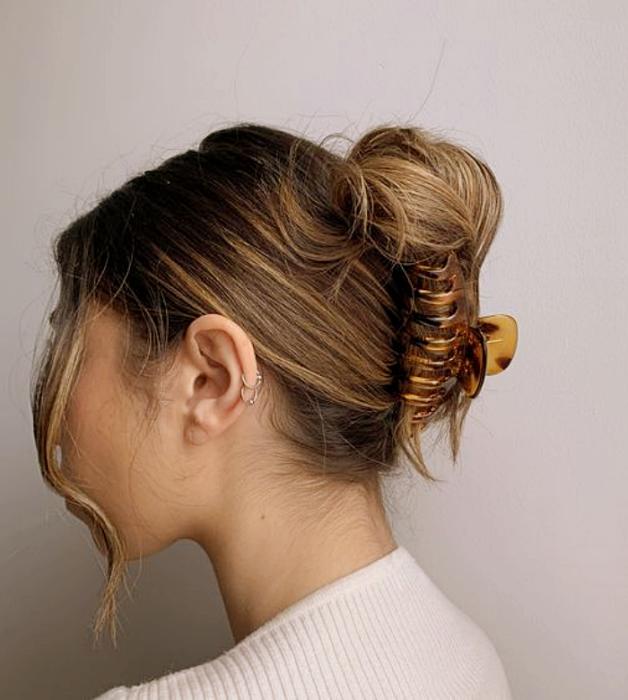 chica de cabello claro usando una pinza tortoise café con beige y ámbar, top blanco