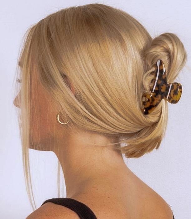 blonde girl with animal print hair clip, black tank top