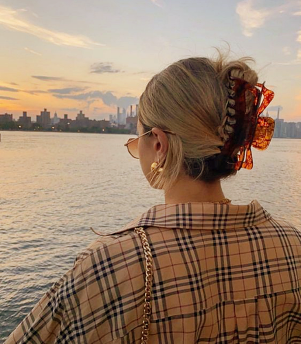 blonde girl with orange hair clip with coffee, beige plaid shirt with blue and red lines