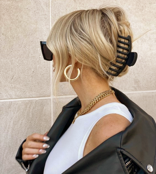 blonde girl with sunglasses, white tank top, gold metal necklace, leather jacket, black hair clip