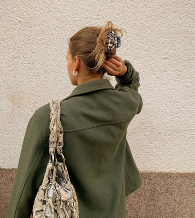 blonde girl with gray hair clip with little flowers, green jacket, beige animal print bag