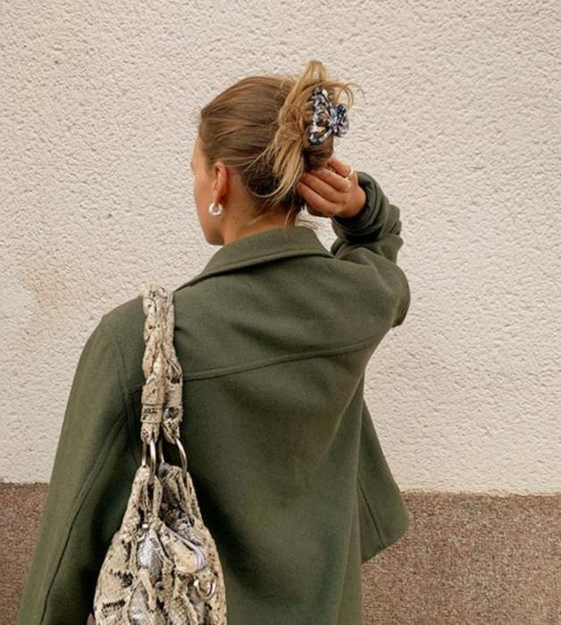 chica rubia con pinza del cabello gris con florecitas, chaqueta verde, bolso beige de animal print