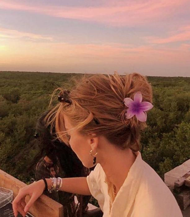 chica rubia con pinza para el cabello color rosa en forma de flor, camisa blanca de manga corta