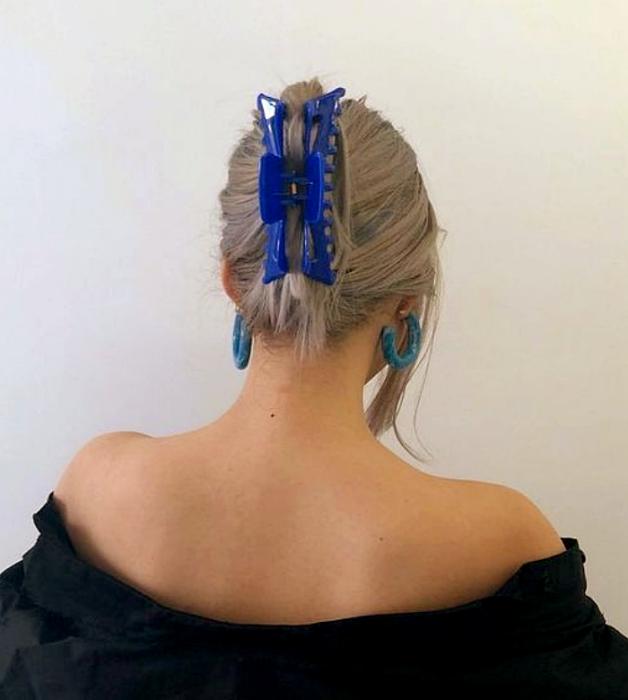 Platinum blonde girl with blue hair clip, off shoulder black blouse