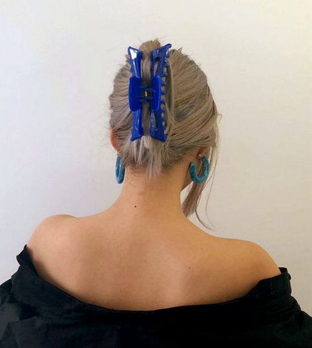 chica rubia platinada con pinza para el cabello azul, blusa negra de hombros caídos