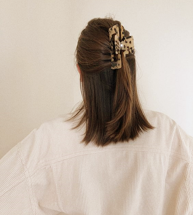 brown haired girl with animal print hair clip, white knitted sweater