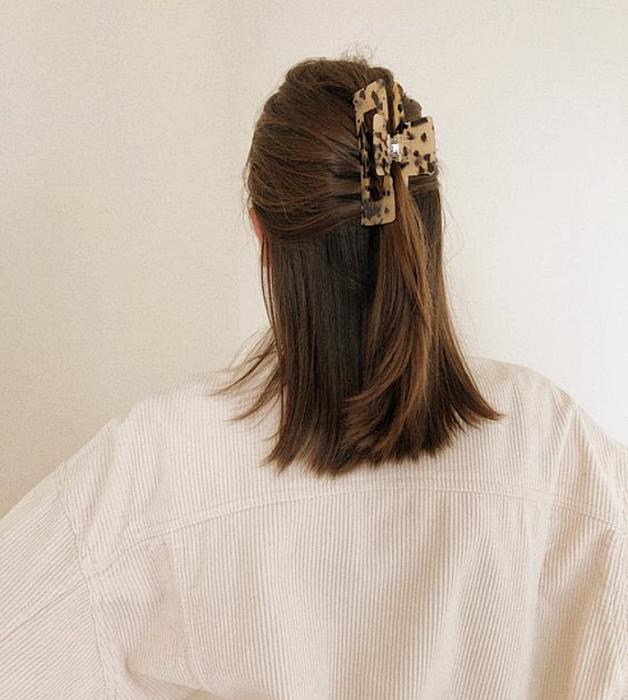 chica de cabello castaño con pinza para el cabello de animal print, suéter tejido blanco