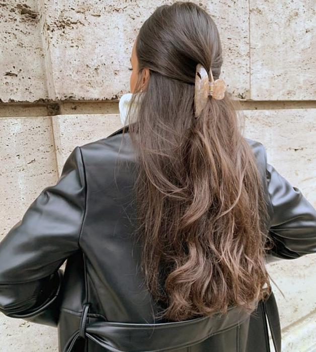chica de cabello largo castaño usando una pinza para el cabello rosa pastel, chamarra de cuero negra