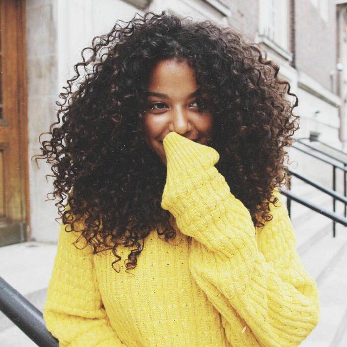 Chica con el cabello rizado usando un suéter amarillo