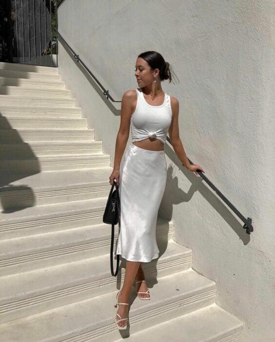 Chica usando una falda de satín en color beige con blusa blanca