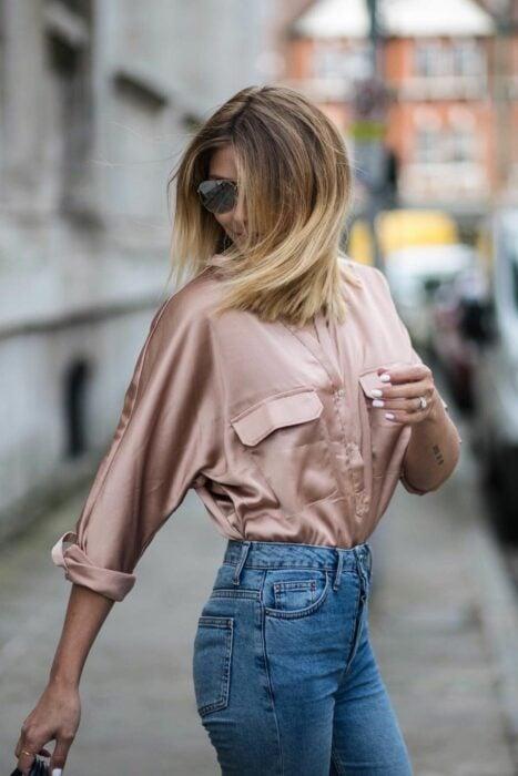 Chica usando una blusa de satín con jeans