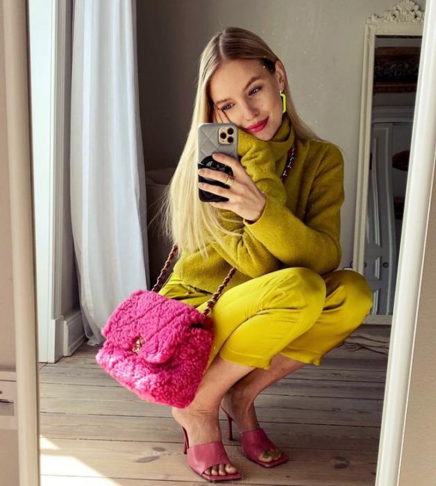 chica rubia con traje de vestir amarillo mostaza, bolso rosa fucsia, tacones sandalias de tacón rosa