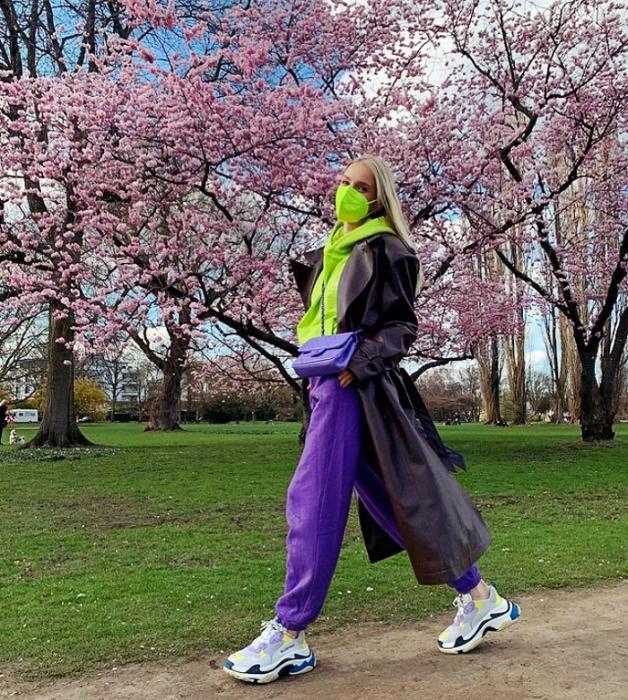 chica rubia con bufanda verde limón, pants morados, tenis blancos con morado, abrigo largo café oscuro