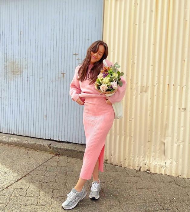 chica de cabello castaño largo usando un vestido tejido rosa ajustado, tenis blancos con gris y flores