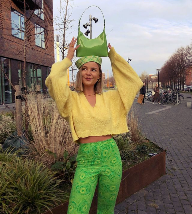 chica rubia con bolso verde pequeño, suéter amarillo holgado, leggings pantalones verdes brillantes