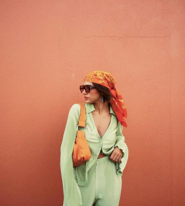 chica de cabello oscuro, lentes de sol oscuros, blusa verde pistache, pantalones holgados pistache, bolso naranja de piel