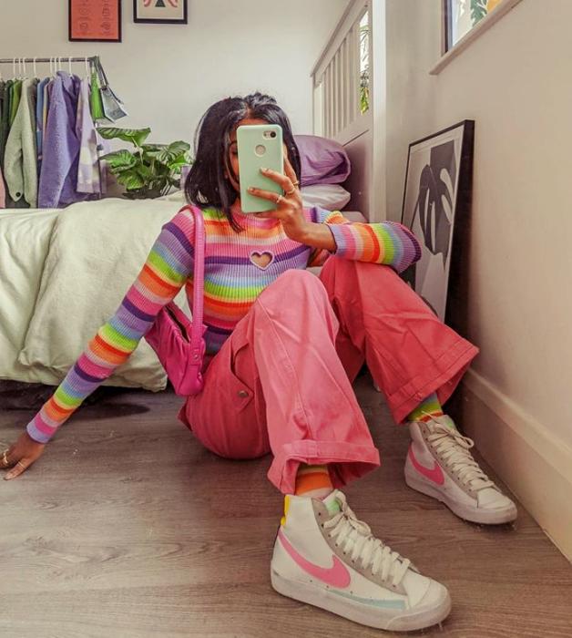 chica morena con cabello oscuro, suéter de arcoíris de manga larga, pantalones rosas acampanados, tenis blancos con rsoas y verde, mochila rosa