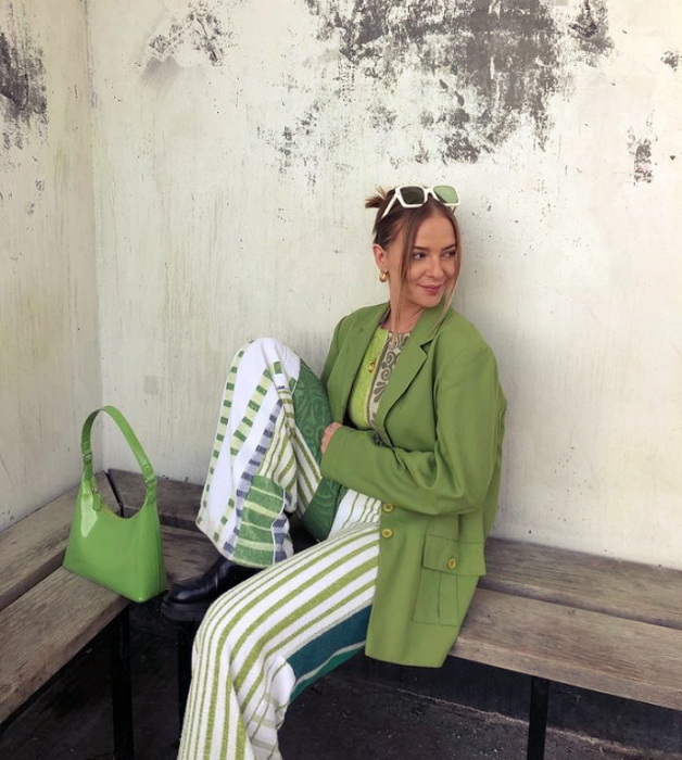 chica de cabello oscuro usando lentes de sol verdes, blazer verde holgado, top verde limón, pantalones blancos con líneas verdes, bolso verde de cuero