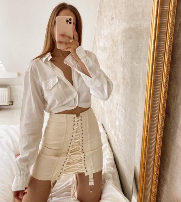 chica con falda beige y top blanco de vestir, cabello claro