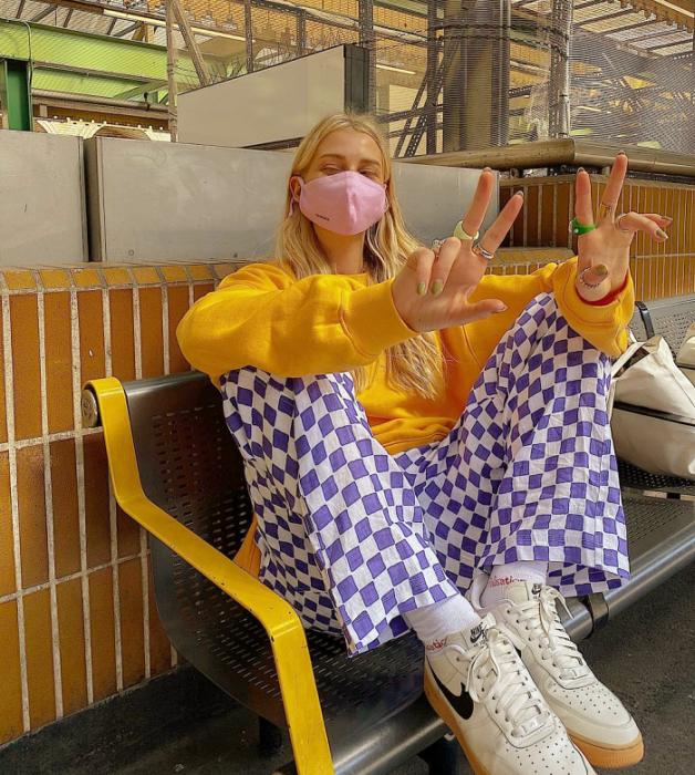 chica rubia con sudadera amarilla, cubrebocas rosa, pantalones azules con cuadros blancos, tenis blancos