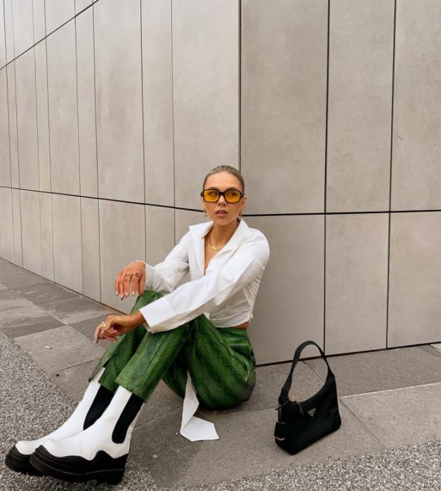 chica de cabello claro con lentes de sol naranjas, blusa blanca de manga larga, pantalones verdes de cuero, botines blancos con negros y bolsa pequeña negra de cuero